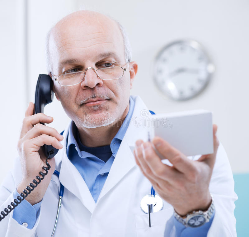 Doctor on the phone. Doctor talking on the phone and looking at medicine's box royalty free stock photo