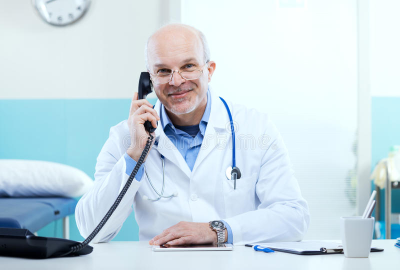 Doctor on the phone. Doctor talking on the phone with medical equipment in the background royalty free stock photos