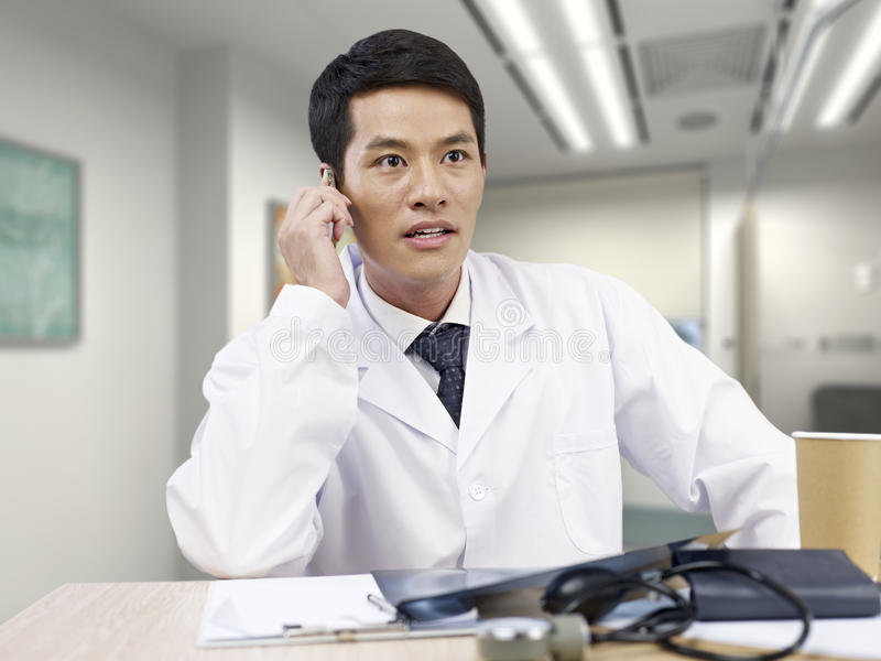 Doctor on the phone. Young asian doctor taking a phone call looking shocked royalty free stock photography