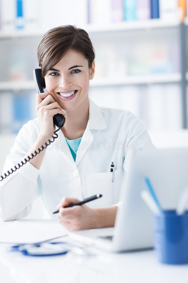 Doctor on the phone. Young female doctor working at office desk and answering phone calls royalty free stock image
