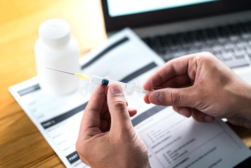 Doctor or physician holding injection needle in dramatic light. Medical research. Health care record document or report paper on table. Vaccine, blood test or stock photography