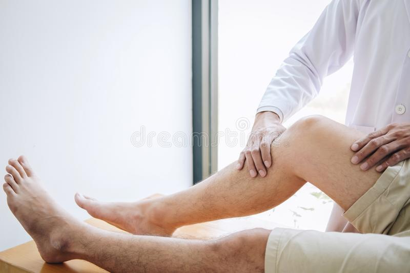 Doctor physiotherapist assisting a male patient while giving exercising treatment massaging the leg of patient in a physio room, royalty free stock photo