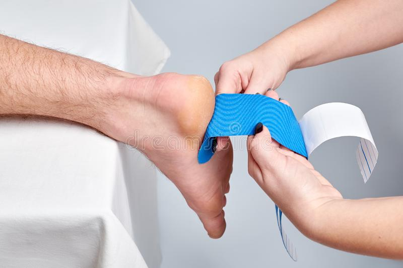 Doctor physiotherapist hands applying kinesio medical taping on the ankle. Of a caucasian man. Closeup view royalty free stock photos