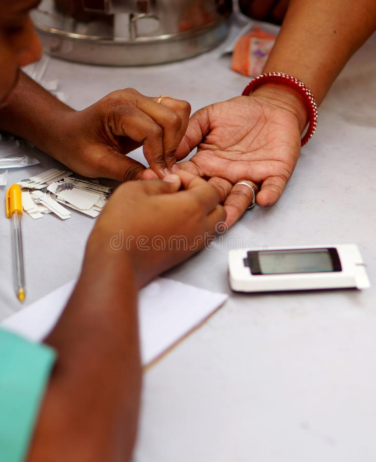 Doctor piercing the finger of woman patient with lancet to check blood sugar leve stock images