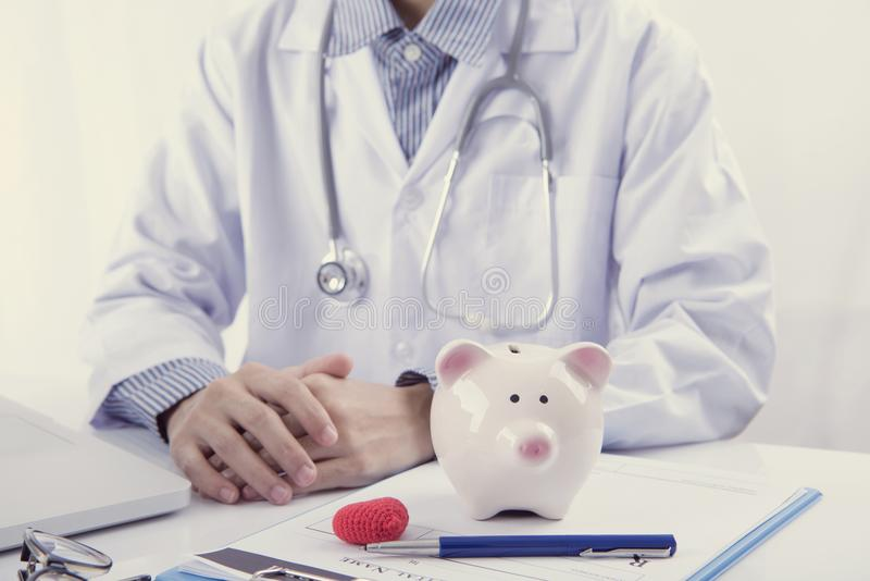 Doctor and piggy bank on table medical fee for health care. royalty free stock photography