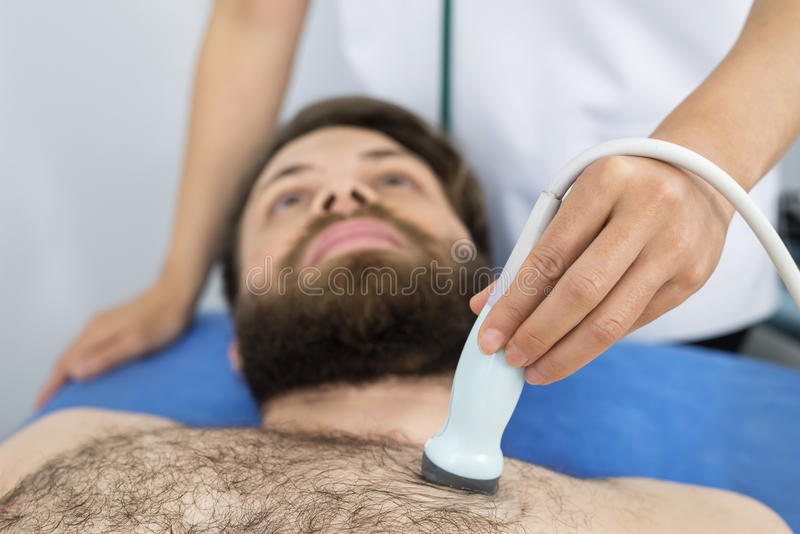 Doctor Placing Ultrasound Probe On Male Patient`s Chest. Midsection of female doctor placing ultrasound probe on male patient`s chest in clinic stock photo