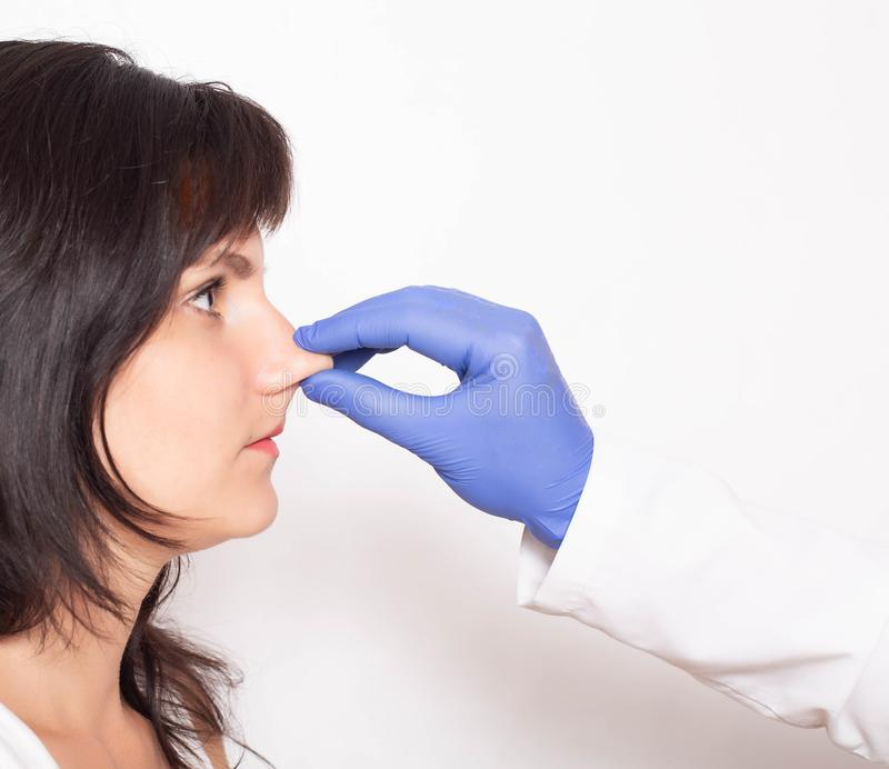 Doctor plastic surgeon examines the patient`s nose before surgery. Rhinoplasty concept of the nose, copy space, secondary. Rhinoplasty, procedure royalty free stock photos