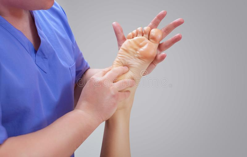 The doctor-podiatrist does an examination and massage of the patient`s foot stock images