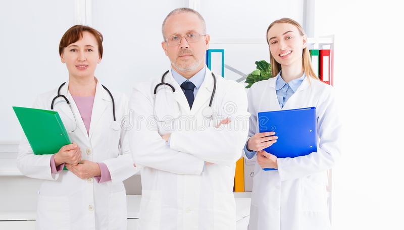 Doctor posing in office with medical staff, he is wearing a stethoscope. Quality medicine concept. Man in white uniform. Medical i. Nsurance. Selective focus royalty free stock images