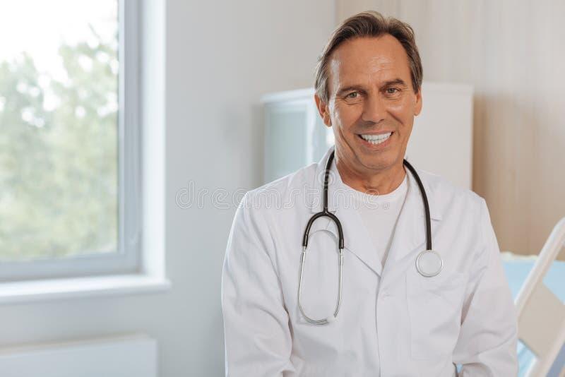 Doctor positivo alegre que le mira fotografía de archivo