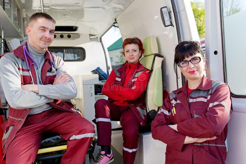 Doctor positivo del ER con los colegas de los paramédicos en coche de la ambulancia foto de archivo