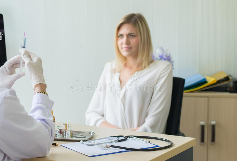 Doctor prepare giving vaccine to scared woman patient with injection or syringe in hospital room stock images