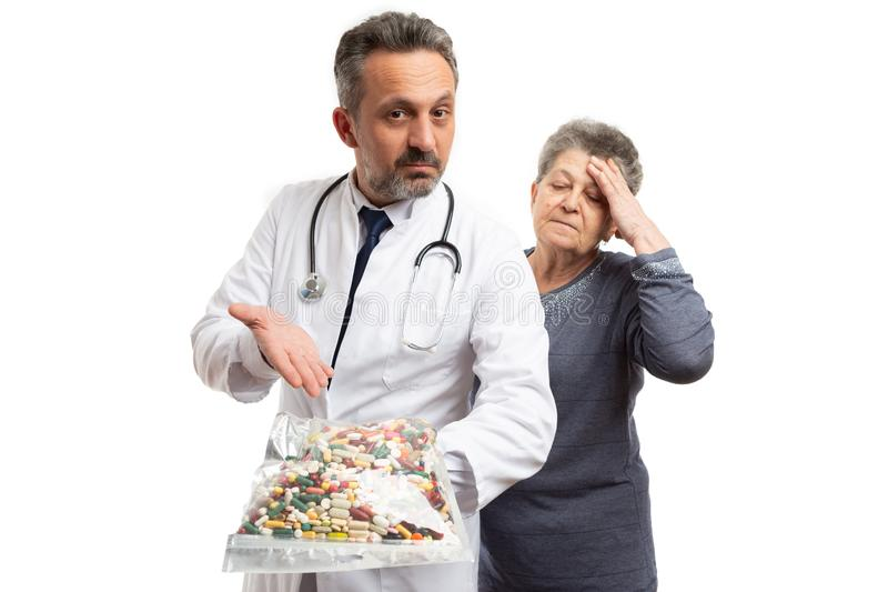 Doctor presenting bag of pills to patient stock photos