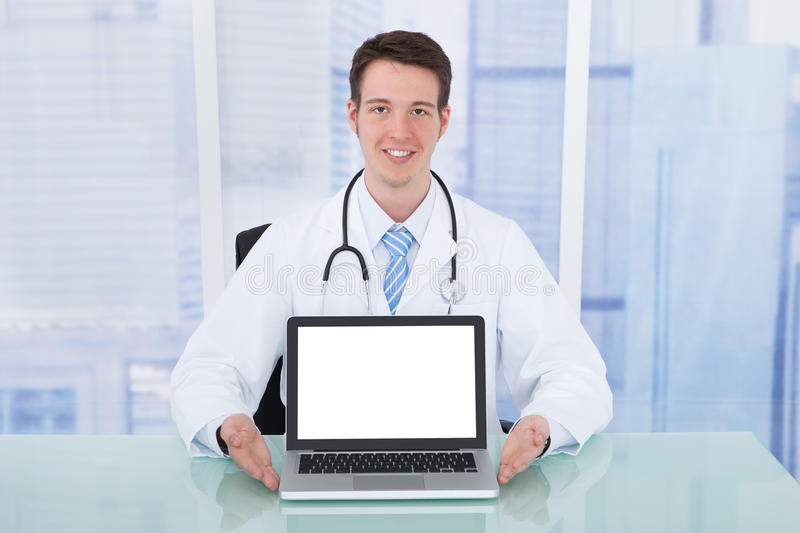 Doctor Presenting Laptop With Blank Screen At Desk royalty free stock images