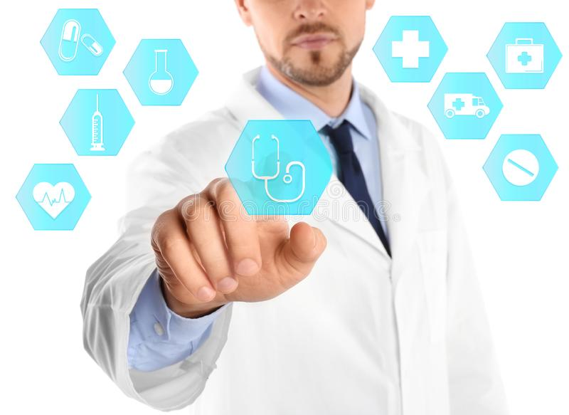 Doctor pressing button on virtual screen against white background. Medical and health insurance concept stock photography