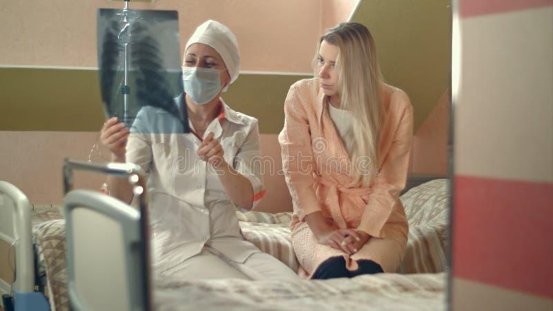 Doctor profesional que lleva a cabo la radiografía y que habla con el paciente femenino joven que se sienta en cama fotos de archivo libres de regalías