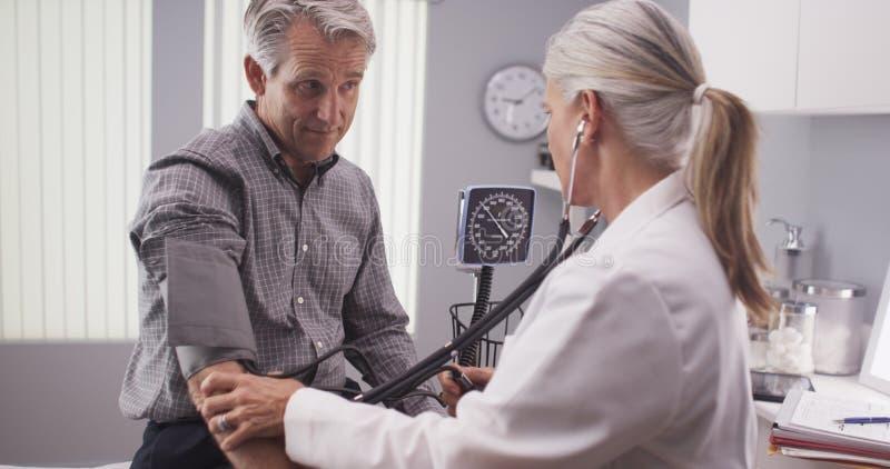 Doctor profesional que mide la presión arterial del hombre mayor fotos de archivo