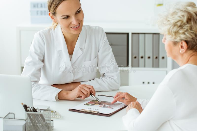 Doctor proposing diet plan. Female doctor proposing balanced diet plan to her patient with overweight royalty free stock images