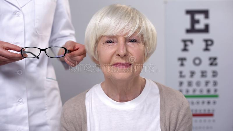 Doctor proposing retired lady new eyeglasses, satisfied patient visiting oculist. Stock photo royalty free stock images
