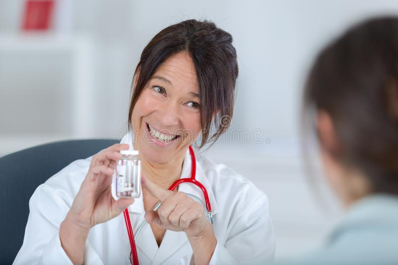 Doctor proposing tablets to patient. Water stock photography