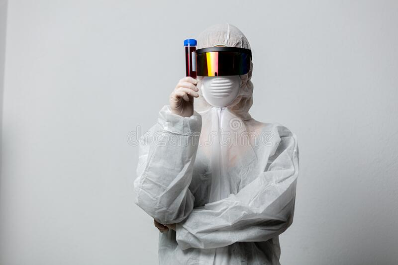 Doctor in protection clothes holds COVID-19 vaccine stock photography
