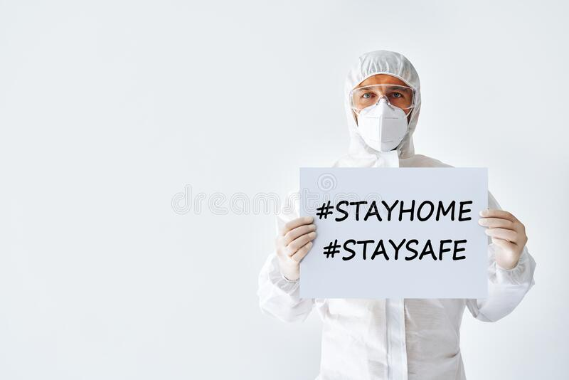 Doctor in protective medical suit showing blank placard stay home, stay safe stock photography
