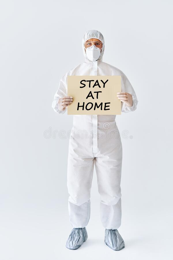 Doctor in protective medical suit showing blank placard stay at home stock photos