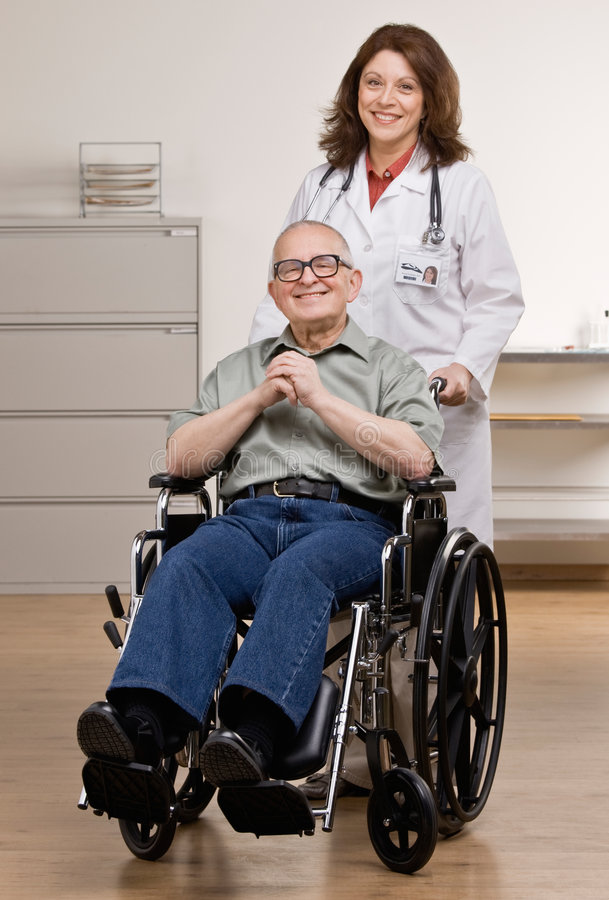 Doctor pushing disabled patient in wheel chair royalty free stock image