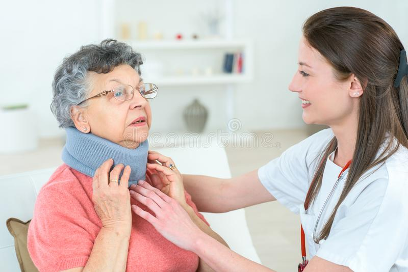 Doctor putting neck brace to elder lady. Doctor royalty free stock photos