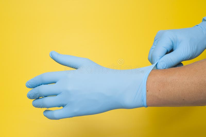 Doctor putting on protective blue gloves isolated on yellow background royalty free stock images