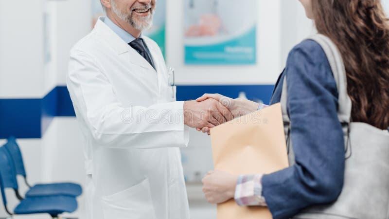 Doctor que acoge con satisfacción a un paciente en la clínica imágenes de archivo libres de regalías