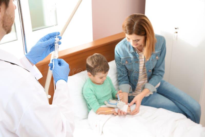 Doctor que ajusta el goteo intravenoso según niño en hospital durante la visita del padre fotografía de archivo