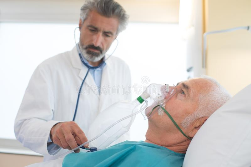 Doctor que ayuda a la máscara de respiración derrumbada del hombre que lleva fotos de archivo libres de regalías