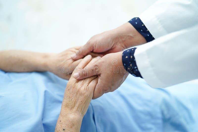 Doctor que celebra el tacto del paciente mayor de las manos o mayor asiático de la mujer de la señora mayor con el amor, cuidado imagen de archivo libre de regalías