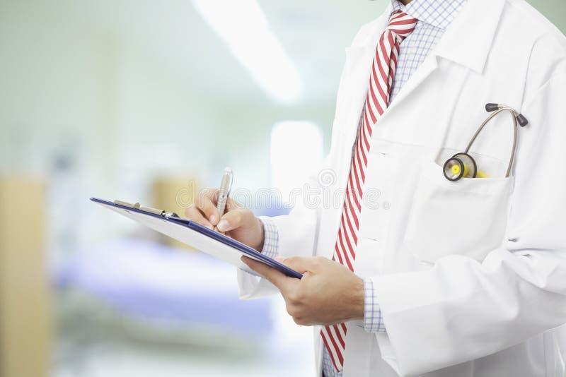 Doctor que completa el documento médico imagen de archivo
