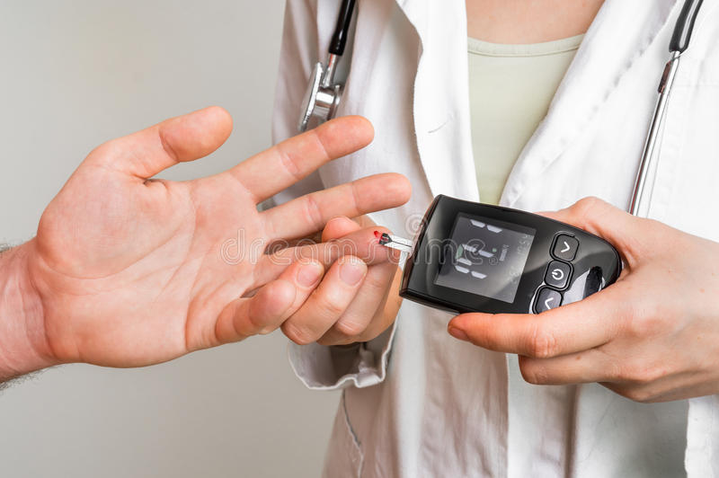 Doctor que comprueba el nivel de azúcar de sangre con glucometer fotografía de archivo libre de regalías
