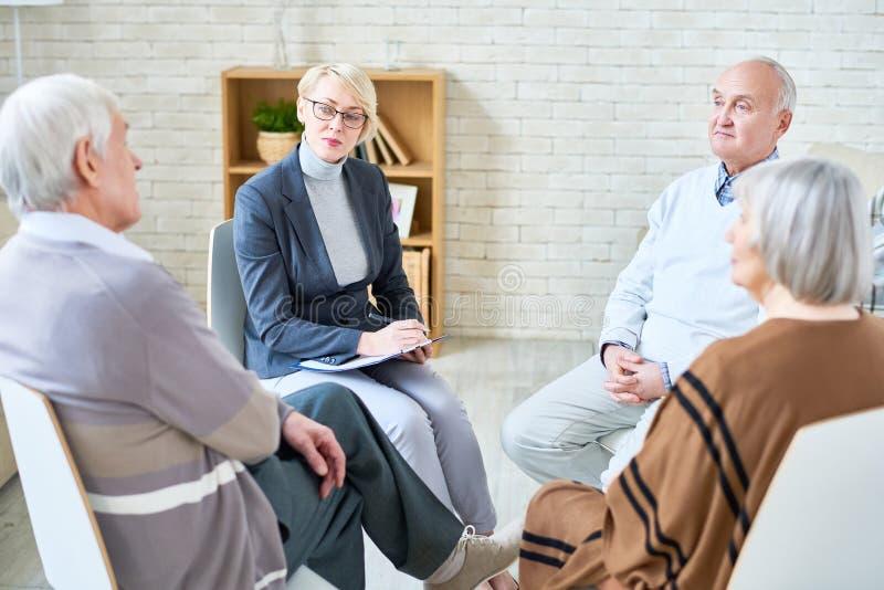 Doctor que consulta a gente mayor en clínica de reposo foto de archivo