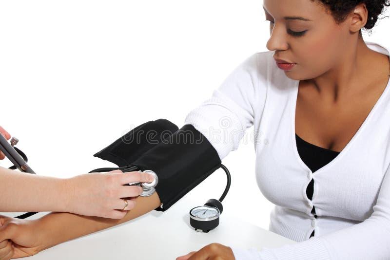 Doctor que controla la presión arterial de la mujer embarazada. imagen de archivo