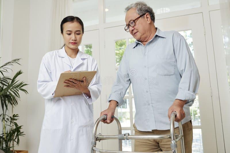 Doctor que controla la salud un paciente mayor imagen de archivo libre de regalías