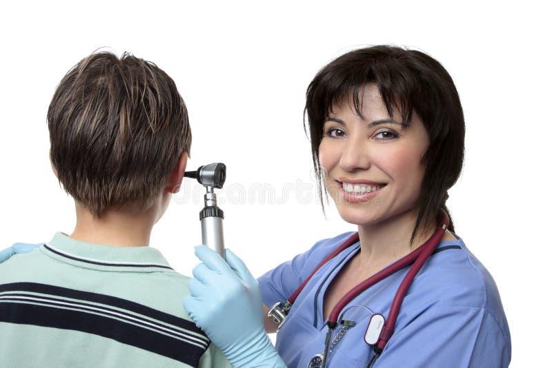 Doctor que controla los oídos con el otoscopio fotografía de archivo libre de regalías