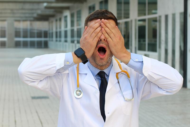 Doctor que cubre sus ojos con las manos fotografía de archivo libre de regalías