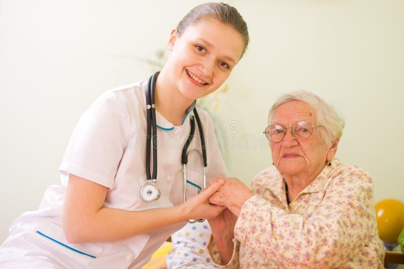 Doctor que cuida con la mujer mayor foto de archivo