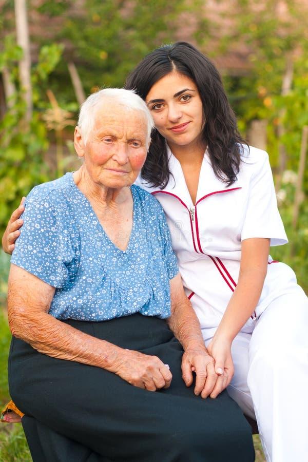 Doctor que cuida con la mujer mayor enferma al aire libre fotos de archivo libres de regalías