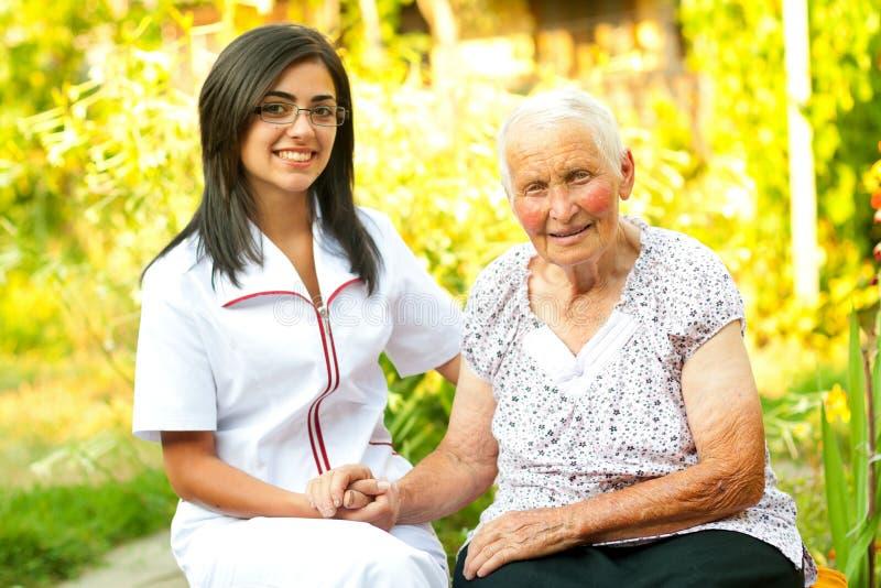 Doctor que cuida con la señora mayor feliz fotografía de archivo libre de regalías