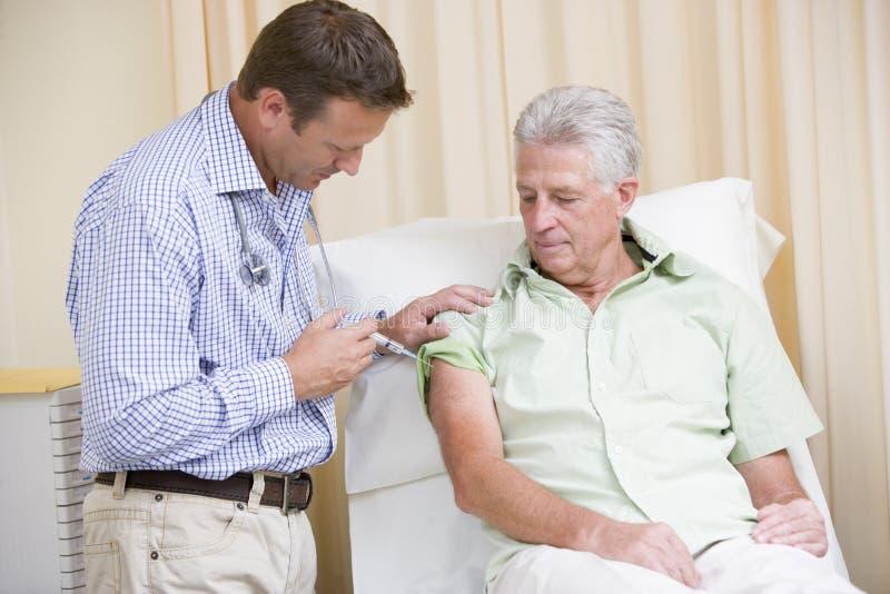 Doctor que da la aguja del hombre en sitio del examen imagen de archivo