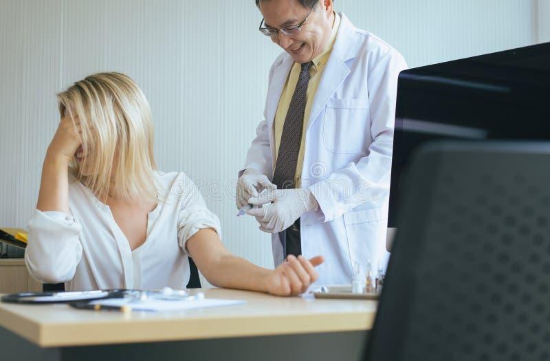 Doctor que da la vacuna al paciente de la mujer con la inyección o a la jeringuilla en sitio de hospital imagen de archivo libre de regalías