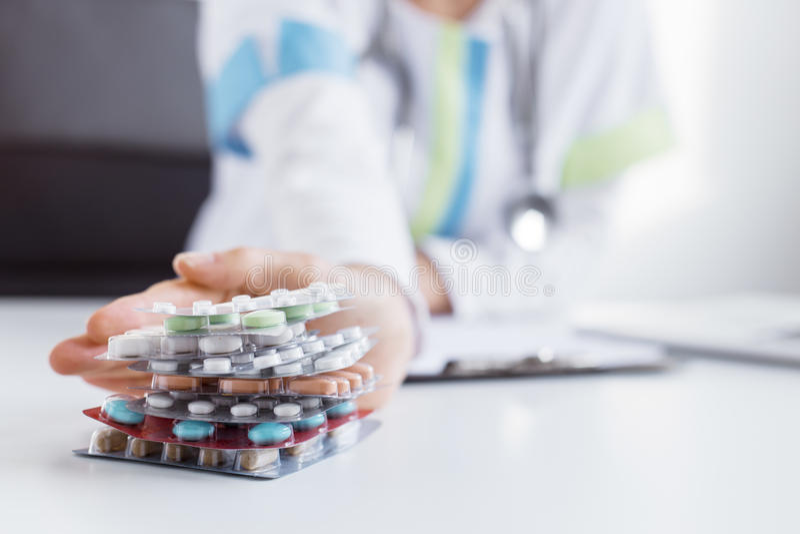 Doctor que da muchas tabletas médicas foto de archivo
