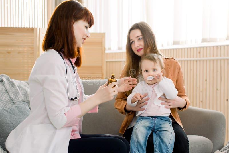 Doctor que da una cuchara del jarabe a la muchacha del niño fotografía de archivo libre de regalías