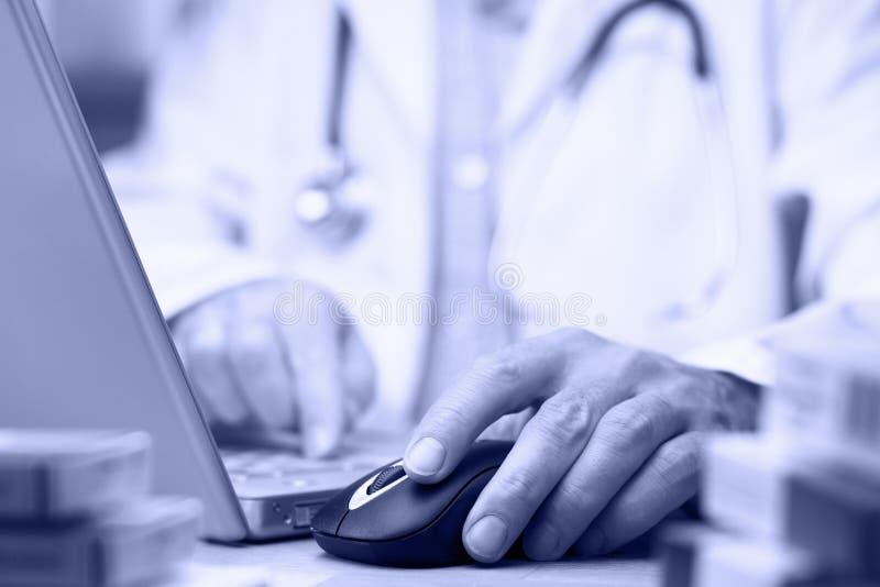 Doctor que elabora el informe médico en línea del Internet foto de archivo libre de regalías