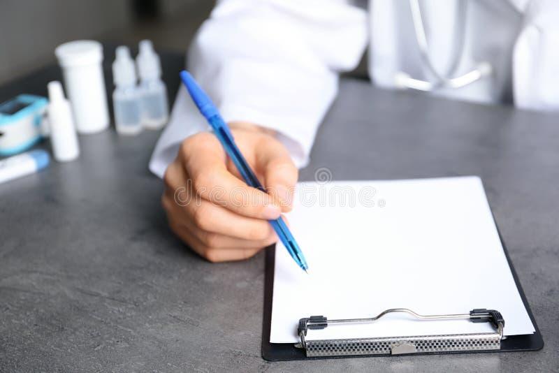 Doctor que escribe en la tabla con diversos objetos médicos imagenes de archivo